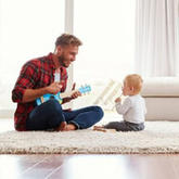 dad playing guitar to child